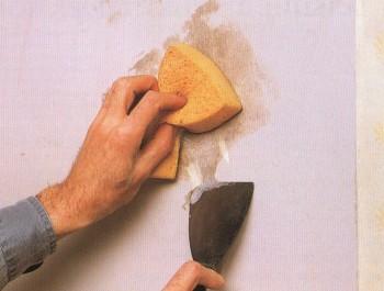 Очистка старой побелки на стене мокрой губкой и шпателем